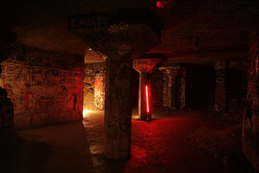 a study shot with a red-shining sara and a strong candle-like source drawing light on walls and columns in an underground location